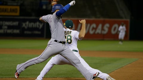 Texas Rangers' Robinson Chirinos runs to first base as Oakland Athletics first baseman Matt Olson fields the throw during the eighth inning of a baseball game Saturday, Sept. 23, 2017, in Oakland, Calif. Chirinos grounded out to Athletics shortstop Marcus Semien on the play. (AP Photo/Eric Risberg)