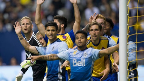 Vancouver Whitecaps goalkeeper David Ousted, left, looks through a crowd of players on a Colorado Rapids corner kick during the first half of an MLS soccer match Saturday, Sept. 23, 2017, in Vancouver, British Columbia. (Darryl Dyck/The Canadian Press via AP)
