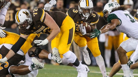 Wyoming running back Milo Hall (3) avoids a tackle from Hawaii linebacker Jahlani Tavai (31) during the first half of an NCAA college football game in Laramie, Wyo., Saturday, Sept. 23, 2017. (AP Photo/Shannon Broderick)