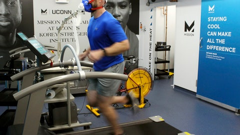 In this Thursday, Sept. 21, 2017 photo, Ryan Curtis, associate director of athlete performance and safety for UConn's Korey Stringer Institute, runs on a treadmill at the institute's Mission Heat Lab in Storrs, Conn. The new $700,000 lab allows scientists to monitor how athletes, soldiers and others respond to temperatures of up to 110 degrees and 90 percent humidity. (AP Photo/Pat Eaton-Robb)
