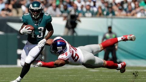 Philadelphia Eagles' Darren Sproles, left, tries to slip past New York Giants' Olivier Vernon during the first half of an NFL football game, Sunday, Sept. 24, 2017, in Philadelphia. (AP Photo/Michael Perez)