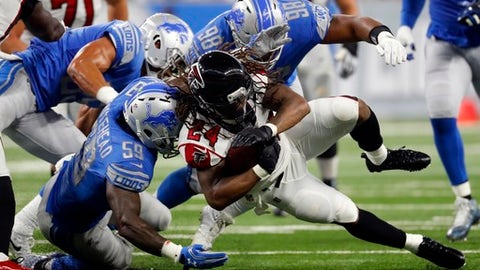 Atlanta Falcons running back Devonta Freeman (24) is tackled by Detroit Lions middle linebacker Tahir Whitehead (59) and defensive end Jeremiah Ledbetter (98) during the first half of an NFL football game, Sunday, Sept. 24, 2017, in Detroit. (AP Photo/Paul Sancya)
