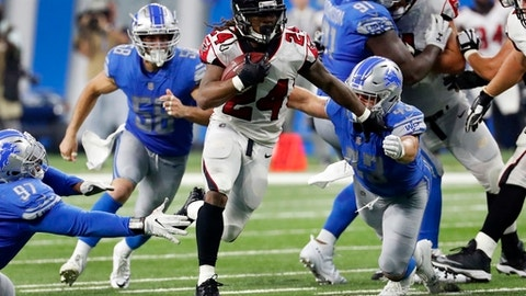 Atlanta Falcons running back Devonta Freeman (24) rushes through the Detroit Lions defense during the first half of an NFL football game, Sunday, Sept. 24, 2017, in Detroit. (AP Photo/Rick Osentoski)