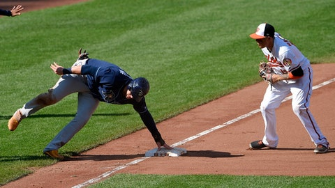 Tampa Bay Rays' Logan Morrison, left, holds on to the bag as he was safe at third next to Baltimore Orioles third baseman Manny Machado (13) on a single by Tampa Bay Rays' Corey Dickerson during the fifth inning of a baseball game, Sunday, Sept. 24, 2017, in Baltimore. (AP Photo/Nick Wass)