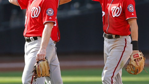 Washington Nationals second baseman Daniel Murphy, left, relief pitcher Brandon Kintzler, center, and shortstop Trea Turner celebrate after the they defeated the New York Mets 3-2 in a baseball game, Sunday, Sept. 24, 2017, in New York. (AP Photo/Kathy Willens)
