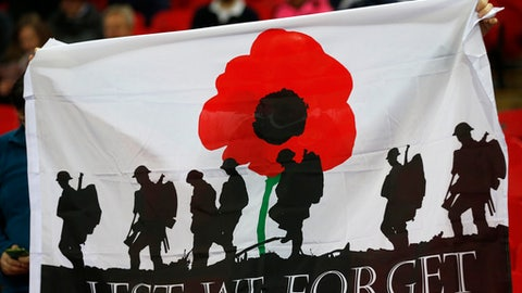 FILE - A Friday, Nov. 11, 2016 file photo showing a banner with the silhouette of troops and a large red poppy with the words 'Lest We Forget' is held up by a fan prior to the start of the World Cup 2018 Group F qualification soccer match between England and Scotland at Wembley stadium in London. FIFA is set to relax the rules that ban teams from commemorating non-sporting events at soccer matches in response to high-profile disputes with British associations over honoring war dead. (AP Photo/Frank Augstein, File)