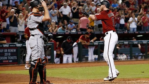 Arizona Diamondbacks' Chris Herrmann, right, points to the crowd as he arrives at home plate after hitting a home run as Miami Marlins' J.T. Realmuto, left, adjusts his catcher's mask during the fifth inning of a baseball game Sunday, Sept. 24, 2017, in Phoenix. (AP Photo/Ross D. Franklin)