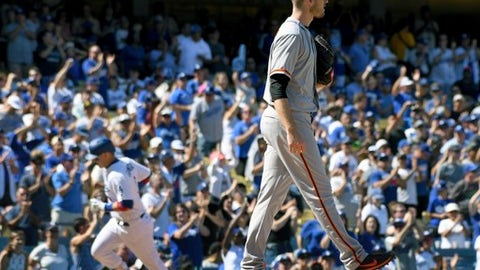 San Francisco Giants pitcher Chris Stratton, right, walks on the mound as Los Angeles Dodgers' Yasmani Grandal, left, rounds the bases after hitting a two-run home run during the fourth inning of a baseball game, Sunday, Sept. 24, 2017, in Los Angeles. (AP Photo/Michael Owen Baker)