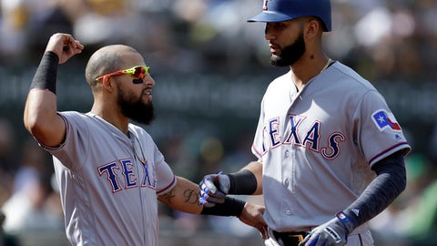 Texas Rangers' Nomar Mazara, right, celebrates with Rougned Odor after hitting a home run against the Oakland Athletics in the seventh inning of a baseball game Sunday, Sept. 24, 2017, in Oakland, Calif. (AP Photo/Ben Margot)
