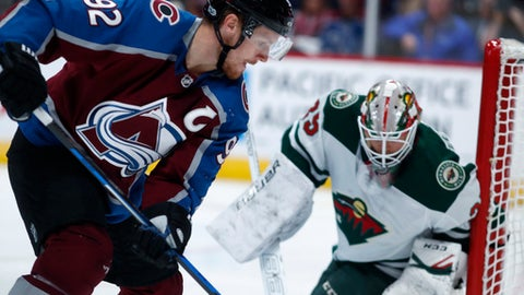 Colorado Avalanche left wing Gabriel Landeskog, front, of Sweden, redirects the puck at Minnesota Wild goalie Niklas Svedberg in the first period of a preseason hockey game, Sunday, Sept. 24, 2017, in Denver. (AP Photo/David Zalubowski)