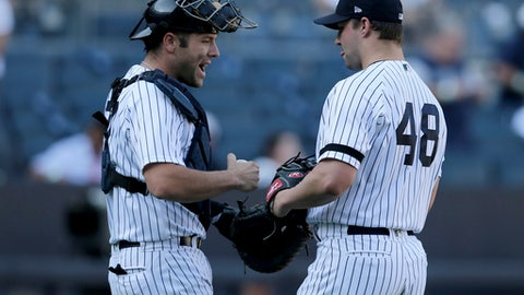 New York Yankees catcher Gary Sanchez, left, and relief pitcher Tommy Kahnle celebrate at the end of the baseball game against the Kansas City Royals at Yankee Stadium, Monday, Sept. 25, 2017, in New York. The Yankees defeated the Royals 11-3. (AP Photo/Seth Wenig)