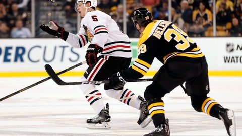 Chicago Blackhawks defenseman Connor Murphy reaches for a loose puck behind Boston Bruins' Matt Beleskey during the first period of an NHL preseason hockey game in Boston, Monday, Sept. 25, 2017. (AP Photo/Winslow Townson)