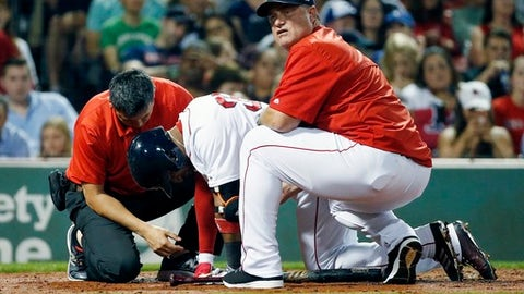 Boston Red Sox manager John Farrell, right, and a trainer tend to Eduardo Nunez after during the third inning of a baseball game against the Toronto Blue Jays in Boston, Monday, Sept. 25, 2017. Nunez was removed from the game after finishing his at-bat. (AP Photo/Michael Dwyer)