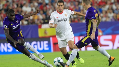 Sevilla's Wissam Ben Yedder, center, challenges for the ball with Maribor's Jean-Claude Billong, left and his teammate Martin Milec during the Champions League Group E soccer match between Sevilla and Maribor at the stadium Ramón Sánchez Pizjuán in Seville, Spain, Tuesday, Sept. 26, 2017. (AP Photo/Miguel Morenatti)