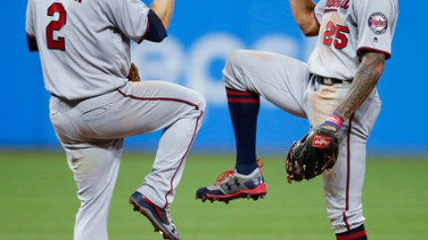 Minnesota Twins' Brian Dozier (2) and Byron Buxton (25) celebrate an 8-6 victory over the Cleveland Indians in a baseball game, Tuesday, Sept. 26, 2017, in Cleveland. (AP Photo/Ron Schwane)