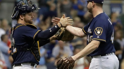 Milwaukee Brewers' Corey Knebel is congratulated by Stephen Vogt after picking up a save during the ninth inning of a baseball game against the Cincinnati Reds Tuesday, Sept. 26, 2017, in Milwaukee. The Brewers won 7-6. (AP Photo/Morry Gash)