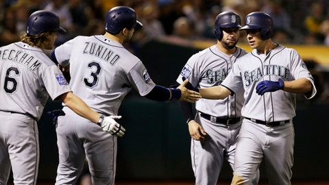 Seattle Mariners' Danny Valencia, right, celebrates with Mike Zunino (3) and Gordon Beckham (6) after hitting a three run home run off Oakland Athletics' Ryan Dull in the seventh inning of a baseball game Tuesday, Sept. 26, 2017, in Oakland, Calif. (AP Photo/Ben Margot)
