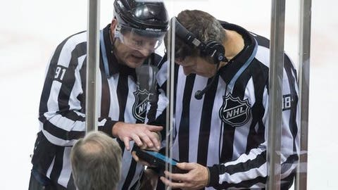 FILE - In this Dec. 3, 2015, file photo, linesmen Don Henderson, left, and Mike Cvik look at a monitor during a coach's challenge by the Vancouver Canucks of an onside call on a goal by Dallas Stars' Patrick Sharp during the third period of an NHL hockey game in Vancouver, British Columbia. The call on the ice stood and the goal was allowed. The NHL has a clear message to coaches this season: Don't challenge an offside call unless you're really, really confident it was wrong. (Darryl Dyck/The Canadian Press via AP, File)