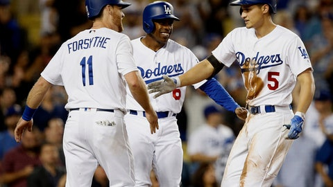 Los Angeles Dodgers' Corey Seager, right, gets congratulations from Logan Forsythe, left, and Curtis Granderson after hitting a three-run home run against the San Diego Padres during the seventh inning of a baseball game in Los Angeles, Tuesday, Sept. 26, 2017. (AP Photo/Alex Gallardo)