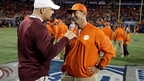 FILE - In this Dec. 3, 2016, file photo, Virginia Tech head coach Justin Fuente, left, speaks to Clemson head coach Dabo Swinney, before the Atlantic Coast Conference championship NCAA college football game in Orlando, Fla. With a quarter of the college football season in the books, 24 undefeated teams remain, along with the possibility that each Power Five conference could have an undefeated champion. That's way off. For now, a couple of cross-divisional conference games matching ranked teams, No. 2 Clemson at No. 12 Virginia Tech and No. 5 Southern California at No. 16 Washington State, highlight the schedule and will be part whittling the field of unbeaten teams. (AP Photo/Chris O' Meara, File)