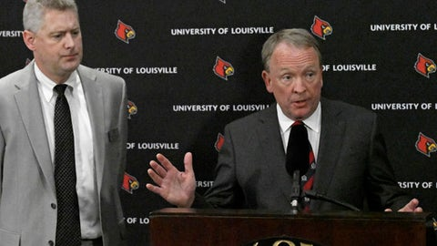 University of Louisville interim President Greg Postel, right, speaks as the university's Director of Media Relations John Karman listens during a press conference Wednesday, Sept. 27, 2017, in Louisville, Ky. Louisville announced Wednesday that they have placed basketball coach Rick Pitino and athletic director Tom Jurich on administrative leave amid a federal bribery investigation.  Jurich is on paid leave, while Pitino is on unpaid leave.  (AP Photo/Timothy D. Easley)