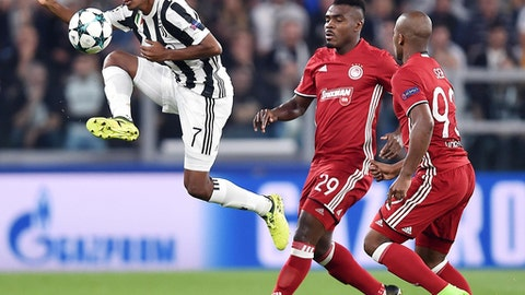 Juventus' Juan Cuadrado, left, goes for the ball ahead of Olympiakos' Emmanuel Emenike and Seb, right, during the Champions League group D soccer match  between Juventus and Olympiakos, at the Allianz stadium in Turin, Italy, Wednesday, Sept. 27, 2017. (Alessandro Di Marco/ANSA via AP)