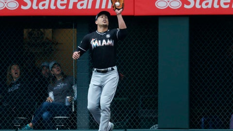 Miami Marlins right fielder Giancarlo Stanton pulls in a fly ball off the bat of Colorado Rockies DJ LeMahieu in the first inning of a baseball game Wednesday, Sept. 27, 2017, in Denver. (AP Photo/David Zalubowski)