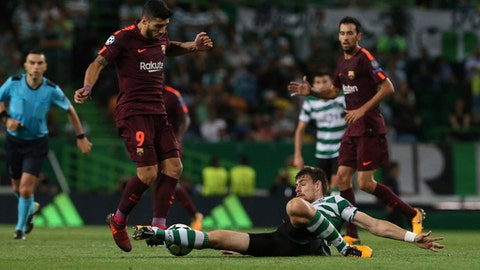 Barcelona's Luis Suarez, left, is challenged by Sporting's Bruno Cesar, during a Champions League, Group D soccer match between Sporting CP and FC Barcelona at the Alvalade stadium in Lisbon, Wednesday Sept. 27, 2017. (AP Photo/Armando Franca)