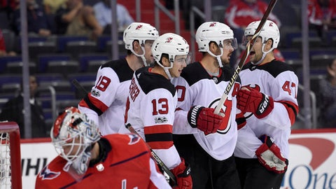 New Jersey Devils center Nico Hischier (13), of Switzerland, celebrates his goal with John Quenneville (47), Marcus Johansson, second from right, and Drew Stafford (18) as Washington Capitals goalie Braden Holtby (70) looks back at the goal during the first period of an NHL preseason hockey game, Wednesday, Sept. 27, 2017, in Washington. (AP Photo/Nick Wass)