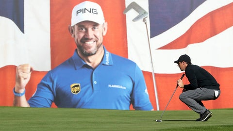 Northern Ireland's Rory McIlroy lines up a putt in front of a larger poster of British golfer Lee westward  on the 18th during day one of the British Masters at Close House Golf Club, Newcastle northeast England Thursday Sept. 28, 2017. (Owen Humphreys/PA via AP)
