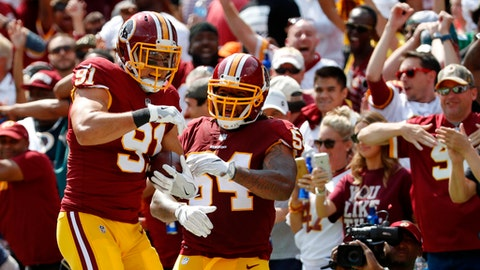 FILE - In this Sept. 10, 2017, file photo, Washington Redskins outside linebacker Ryan Kerrigan, left, celebrates with Mason Foster after running an interception back for a touchdown in the first half of an NFL football game against the Philadelphia Eagles in Landover, Md. The Redskins bring the league's fifth-rated defense into Kansas City after it held the Raiders to 128 yards total offense last week. (AP Photo/Alex Brandon, File)
