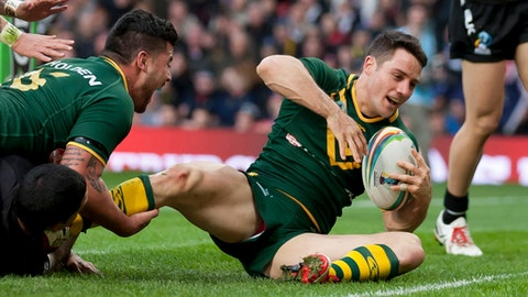 FILE - In this Nov. 30, 2013, file photo, Australia's Cooper Cronk scores a disallowed try during his team's World Cup Final International Rugby League match against New Zealand at Old Trafford Stadium, Manchester, England. On Sunday, Oct. 1, 2017, the Melbourne Storm take on the upstart North Queensland Cowboys in their title match at Sydney's Olympic stadium. The Storm hope to send off retiring halfback Cronk as premiership winner. (AP Photo/Jon Super, File)