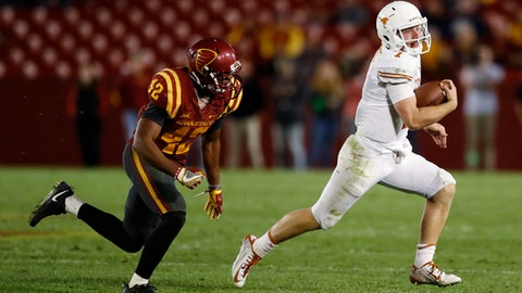 Texas quarterback Shane Buechele runs from Iowa State linebacker Marcel Spears Jr., left, during the second half of an NCAA college football game, Thursday, Sept. 28, 2017, in Ames, Iowa. Texas won 17-7. (AP Photo/Charlie Neibergall)