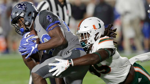 Miami's Mike Smith, right, reaches to tackle Duke's Brittain Brown during the first half of an NCAA college football game in Durham, N.C., Friday, Sept. 29, 2017. (AP Photo/Gerry Broome)
