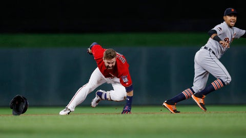 Detroit Tigers shortstop Dixon Machado, right, watches as Minnesota Twins' Brian Dozier stumbles after crossing second base while trying for a triple during the first inning of a baseball game Friday, Sept. 29, 2017, in Minneapolis. Dozier returned safely to second. (AP Photo/Jim Mone)
