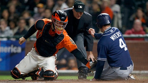 San Diego Padres' Wil Myers (4) is tagged out at home plate by San Francisco Giants catcher Nick Hundley (5) during the third inning of a baseball game Friday, Sept. 29, 2017, in San Francisco. (AP Photo/Tony Avelar)