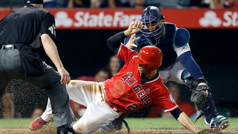 Los Angeles Angels' Andrelton Simmons, center, slides in safely, as Seattle Mariners catcher Mike Zunino misses the throw from the outfield on a sacrifice fly by Cliff Pennington during the fourth inning of a baseball game in Anaheim, Calif., Friday, Sept. 29, 2017. (AP Photo/Alex Gallardo)
