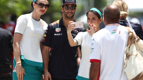 Red Bull Racing driver Daniel Ricciardo of Australia, center, takes selfie with the fans during the third practice and qualifying round for the Malaysian Formula One Grand Prix in Sepang, Malaysia, Saturday, Sept. 30, 2017. (AP Photo/Daniel Chan)