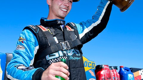 In this Sunday, May 21, 2017 photo, pro stock driver Tanner Gray lifts his trophy into the air after winning the NHRA Menards Heartland Nationals at Heartland Park in Topeka, Kan. Gray defeated Jeg Coughlin in the finals with a pass of 6.580 at 210.87 mph. (Chris Neal/The Topeka Capital-Journal via AP)