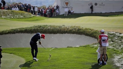 Dustin Johnson hits on the 13th green during the third day of the Presidents Cup at Liberty National Golf Club in Jersey City, N.J., Saturday, Sept. 30, 2017. (AP Photo/Julio Cortez)
