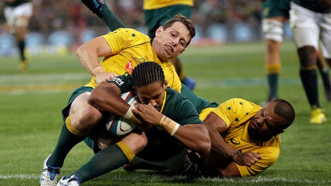 South Africa's Courtnall Skosan' front, scores a try as Australia's Bernard Foley, left, and teammate Kurtley Beale, defend during the Rugby Championship match between South Africa and Australia, at the Free State Stadium in Bloemfontein, South Africa, Saturday, Sept. 30, 2017. (AP Photo/Themba Hadebe)
