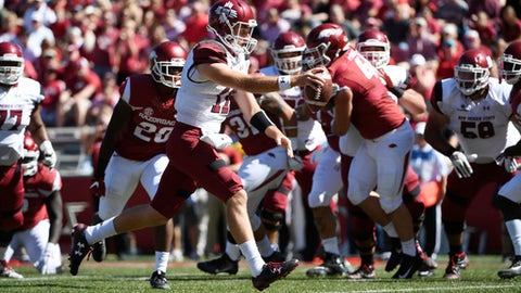 New Mexico State quarterback Tyler Rogers slips past the Arkansas defense to score a touchdown during the first half of an NCAA college football game in Fayetteville, Ark., Saturday, Sept. 30 2017. (AP Photo/Michael Woods)