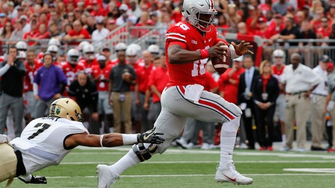 Ohio State quarterback J.T. Barrett, right, scores a touchdown past Army defensive back Jaylon McClinton during the first half of an NCAA college football game Saturday, Sept. 16, 2017, in Columbus, Ohio. (AP Photo/Jay LaPrete)