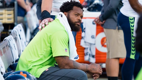 Aug 31, 2017; Oakland, CA, USA; Seattle Seahawks defensive end Michael Bennett (72) sits on the bench during the national anthem, as center Justin Britt (68) puts a hand on his back before the game against the Oakland Raiders at Oakland Coliseum. Mandatory Credit: Kelley L Cox-USA TODAY Sports