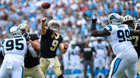 Sep 24, 2017; Charlotte, NC, USA; New Orleans Saints quarterback Drew Brees (9) throws a touchdown pass as Carolina Panthers defensive end Charles Johnson (95) and defensive tackle Kawann Short (99) defend in the first quarter at Bank of America Stadium. Mandatory Credit: Bob Donnan-USA TODAY Sports