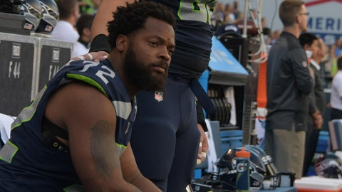 Aug 25, 2017; Seattle, WA, USA; Seattle Seahawks defensive end Michael Bennett (72) sits on the bench with center Justin Britt (68) standing by his side during the playing of the national anthem before a NFL football game against the Kansas City Chiefs at CenturyLink Field. Mandatory Credit: Kirby Lee-USA TODAY Sports
