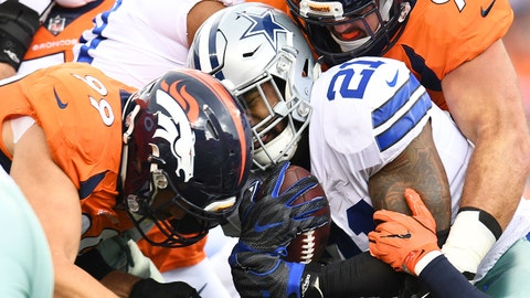 Sep 17, 2017; Denver, CO, USA; Dallas Cowboys running back Ezekiel Elliott (21) is tackled by Denver Broncos defensive end Adam Gotsis (99) and Denver Broncos defensive end Derek Wolfe (95) in the first quarter at Sports Authority Field at Mile High. Mandatory Credit: Ron Chenoy-USA TODAY Sports