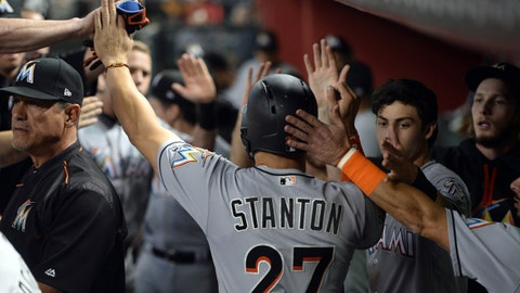 Sep 23, 2017; Phoenix, AZ, USA; Miami Marlins right fielder Giancarlo Stanton (27) celebrates with teammates in the dugout after scoring a run against the Arizona Diamondbacks during the third inning at Chase Field. Mandatory Credit: Joe Camporeale-USA TODAY Sports