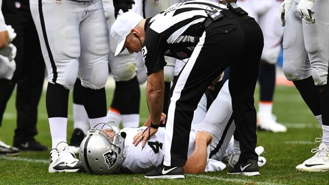 Oct 1, 2017; Denver, CO, USA; NFL referee John Parry (132) checks on an injury to Oakland Raiders quarterback Derek Carr (4) in the second half against the Denver Broncos at Sports Authority Field at Mile High. Mandatory Credit: Ron Chenoy-USA TODAY Sports