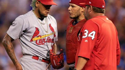 St. Louis Cardinals starting pitcher Carlos Martinez, left, talks with pitching coach Derek Lilliquist (34) and catcher Yadier Molina, back, during the sixth inning of a baseball game against the Kansas City Royals at Kauffman Stadium in Kansas City, Mo., Monday, Aug. 7, 2017. (AP Photo/Orlin Wagner)